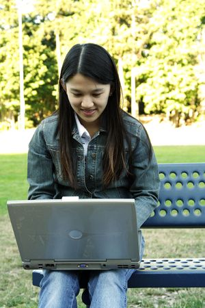 A girl working with her laptop in a park photo