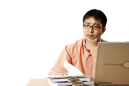 Busy businessman with laptop and a stack of paper photo