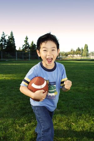 children at play: A happy boy playing football outdoor Stock Photo