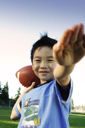 jugando futbol: Un ni�o jugando al f�tbol al aire libre  Foto de archivo