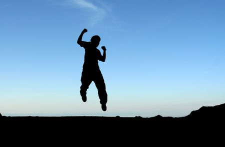 gymnastics silhouette: A happy man jumping in the air, in silhouette Stock Photo