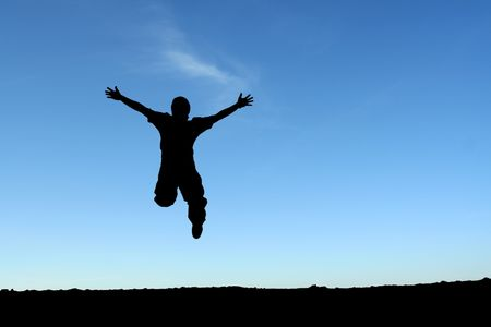 A happy man jumping in the air, in silhouette Stock Photo