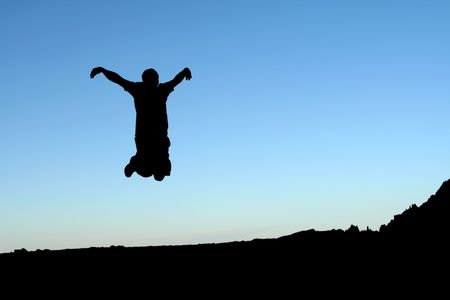 A man jumping in the air, in silhouette photo