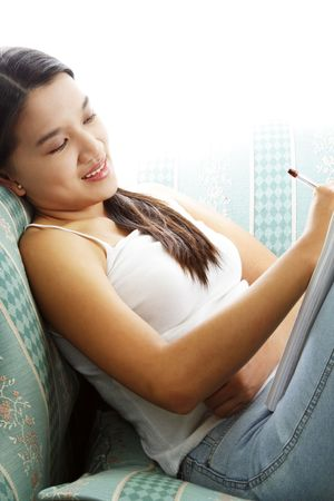 scholarly: A young girl lying on a sofa thinking and writing