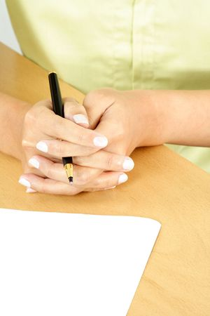 A businesswoman holding a pen ready to write on a piece of blank paper photo