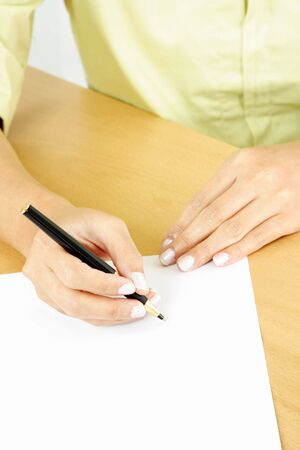 A businesswoman writing on a piece of blank paper photo