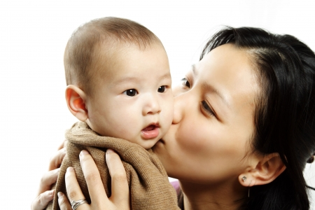 A mother kissing her cute baby son Stock Photo - 598758
