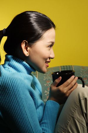 A beautiful young woman sitting on a sofa holding a hot coffee cup Stock Photo - 605209
