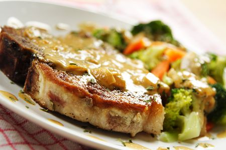 pork chop: A pan fried pork chop with vegetables and coconut sauce Stock Photo