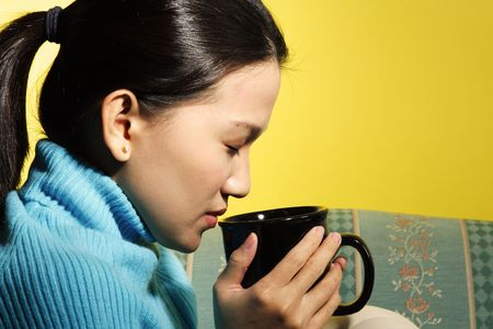 sip: A young woman holding and enjoying her hot drink