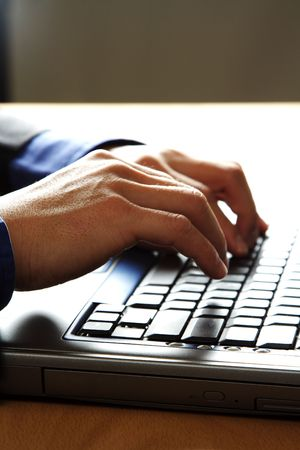 Businessman working and typing on his laptop