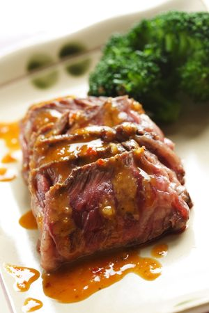 Slices of tender beef served with peanut sauce and vegetables photo