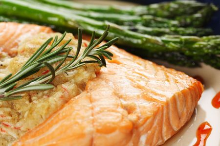 A baked stuffed salmon with asparagus on the side Stock Photo