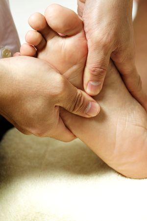 masseuse: A masseuse massaging the feet of a woman