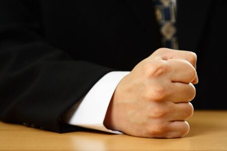 A businessman with his firm fist on a table