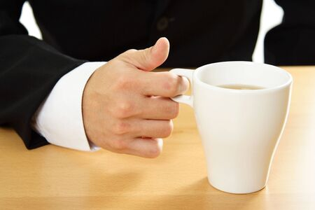 A businessman holding a cup of coffee photo