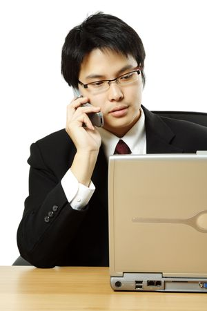 A businessman making a phone call and working on his laptop photo