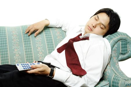 tv remote: A businessman sleeping on a couch holding a TV remote