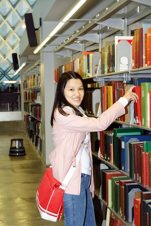 A student getting a book in a library photo