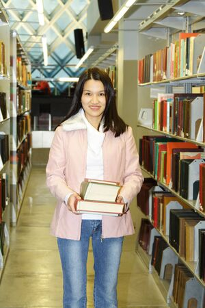 A student carrying books in a library Stock Photo - 697399