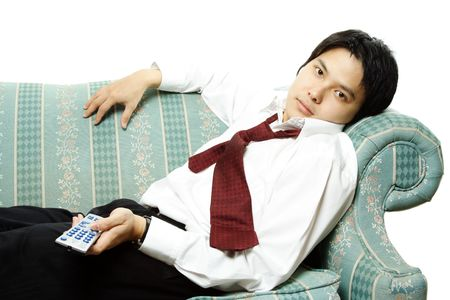 A businessman lying on a sofa holding a television remote photo