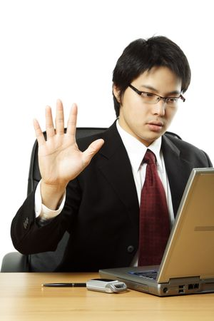 A businessman working on his laptop with his hand up photo