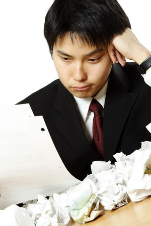 corporate waste: A stressed out businessman with crumpled paper all over table