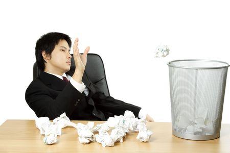 A businessman throwing trash paper into waste basket