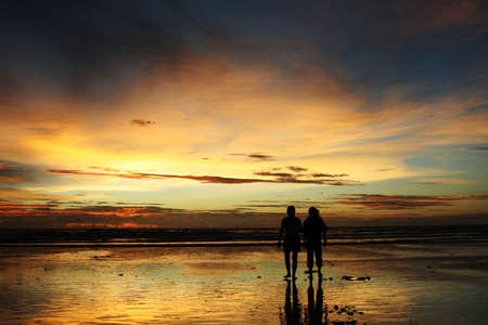 Two people in silhouette walking on a beach during sunset