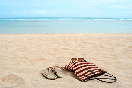 A pair of sandals and sunglasses on a sandy tropical beach photo