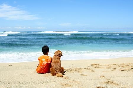 A boy and a dog sitting on the beach Stock Photo