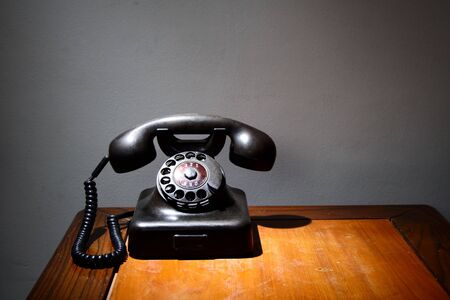 An old black telephone on an old table