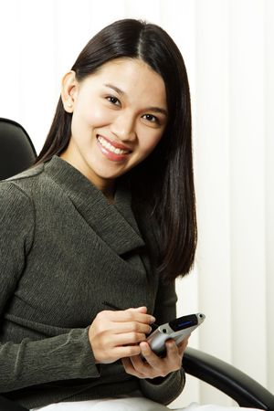 A businesswoman using her PDA at the office Stock Photo - 900676