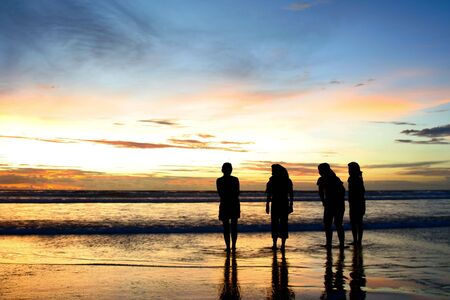 Silhouette shots of four girls on the beach enjoying the dramatic sunset Stock Photo - 914559