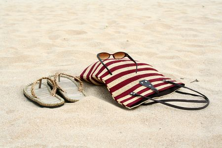 tote: A pair of sandals, sunglasses and a travel tote on the sandy beach