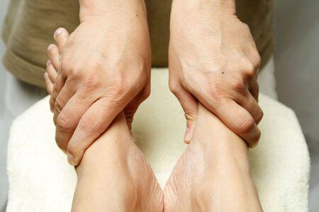 A masseuse massaging the feet of a woman
