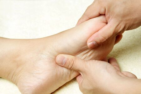 masseuse: A masseuse massaging the foot of a woman