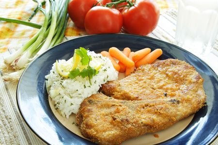 A baked pork chop with rice and carrots photo