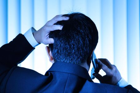 businessman talking: A stressed businessman talking on the phone (in blue tone)