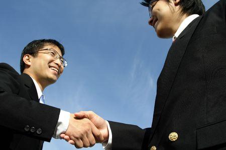 n�gocier: Deux hommes daffaires se serrant la main (foyer sur la main) Banque d'images