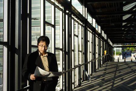 estacion de tren: Un hombre de negocios que leer un peri�dico financiero en la estaci�n de tren  Foto de archivo
