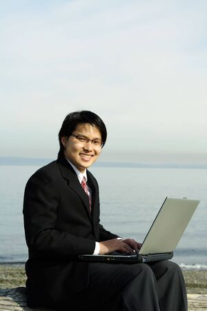 Businessman working on his laptop at the beach photo