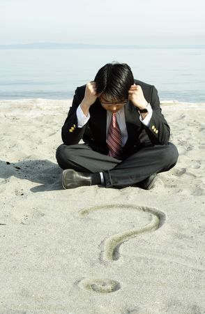 A stressed businessman sitting on the beach with question mark on the sand