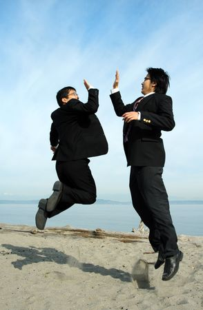 Two businessmen jumping happily on the beach