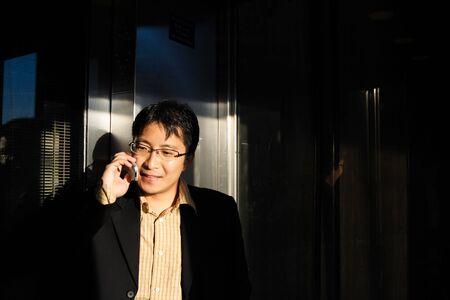 A businessman talking on the phone inside an elevator Stock Photo - 989499