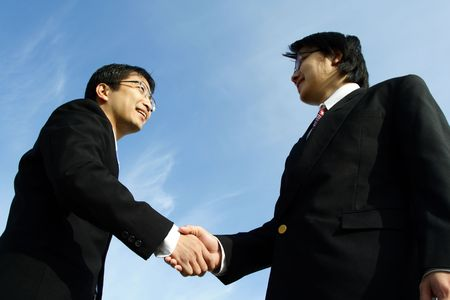 Two businessmen shaking hands on a deal (focus on the hands) photo