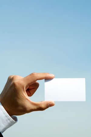 A businessman holding a blank business card outdoor