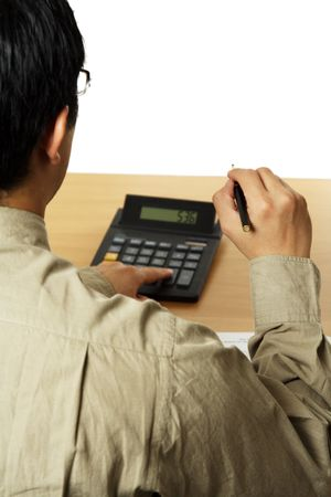 A businessman holding a pen and using a calculator Stock Photo - 1017541