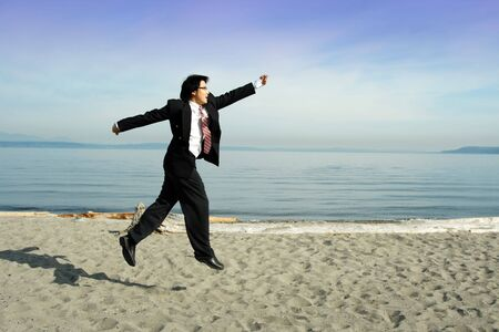 A businessman jumping celebrating happily at the beach photo
