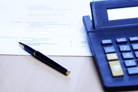 An image of a pen and a calculator on top of a financial statement, can be used for business finance and accounting concept ( shot in blue tone) photo